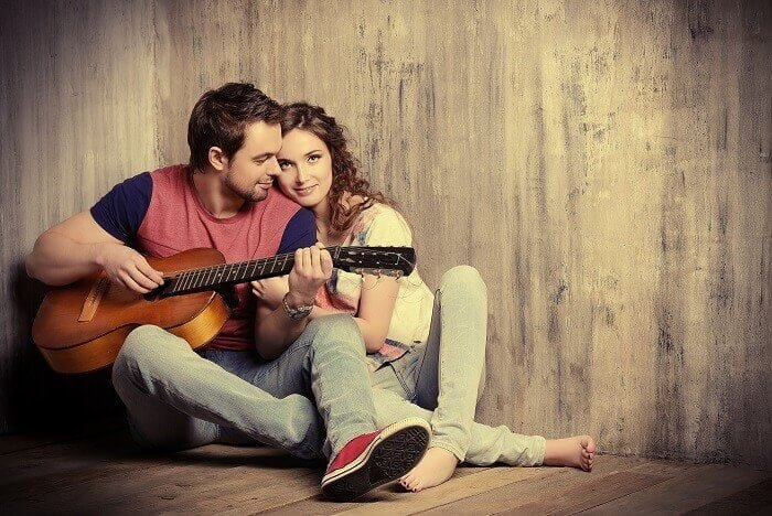 man playing guitar for woman